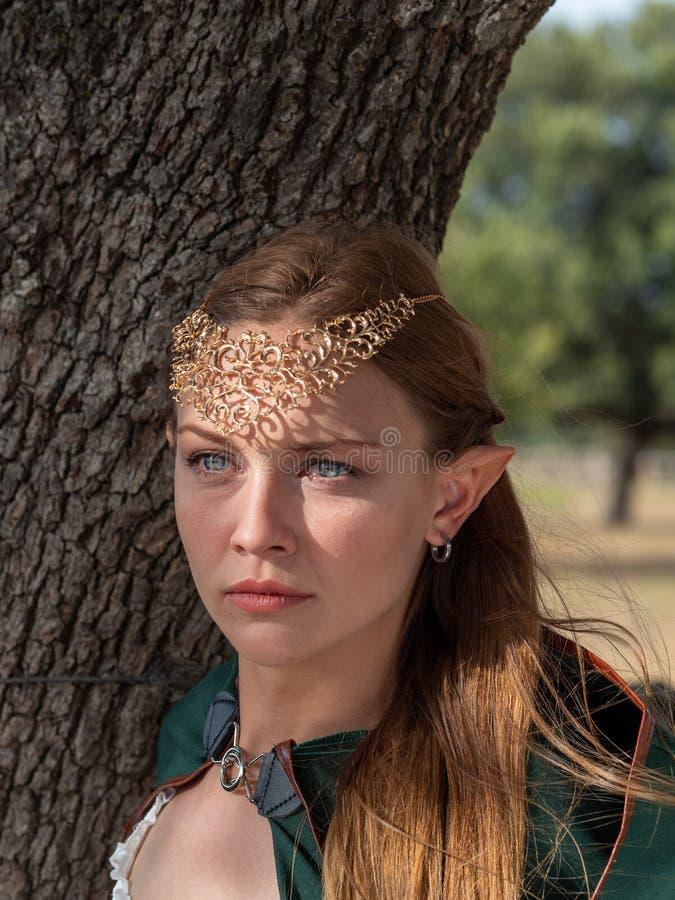 Close-up da menina loura com os olhos azuis e as orelhas do duende que vestem um cabo verde imagens de stock royalty free