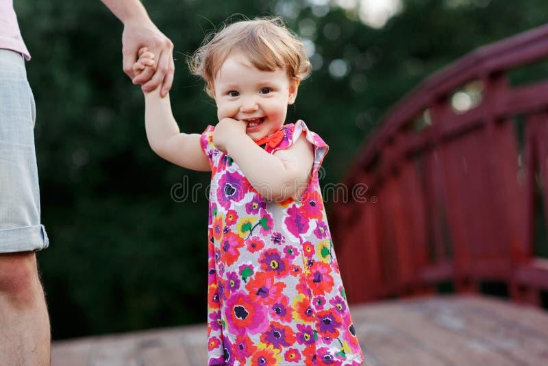 Close up da menina que guarda Dad& x27; mão de s na ponte imagem de stock