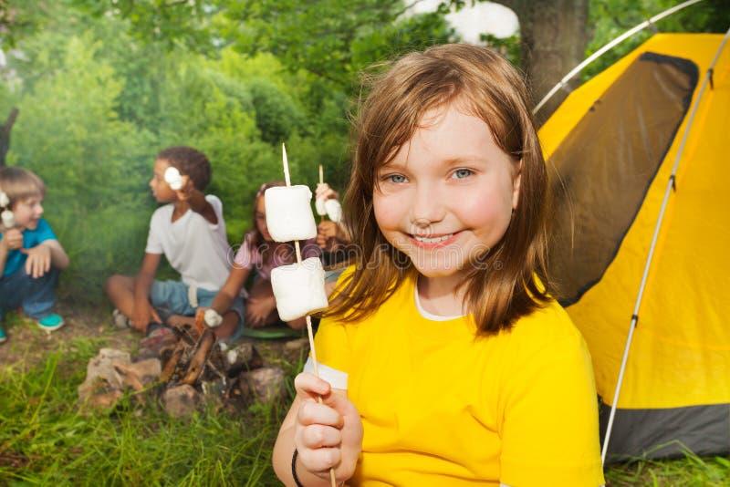 Close-up da menina que guarda a vara com marshmallows foto de stock