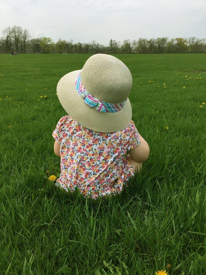 Close up da menina que senta-se na grama em um parque que veste um chapéu de palha e que olha fora na distância imagens de stock