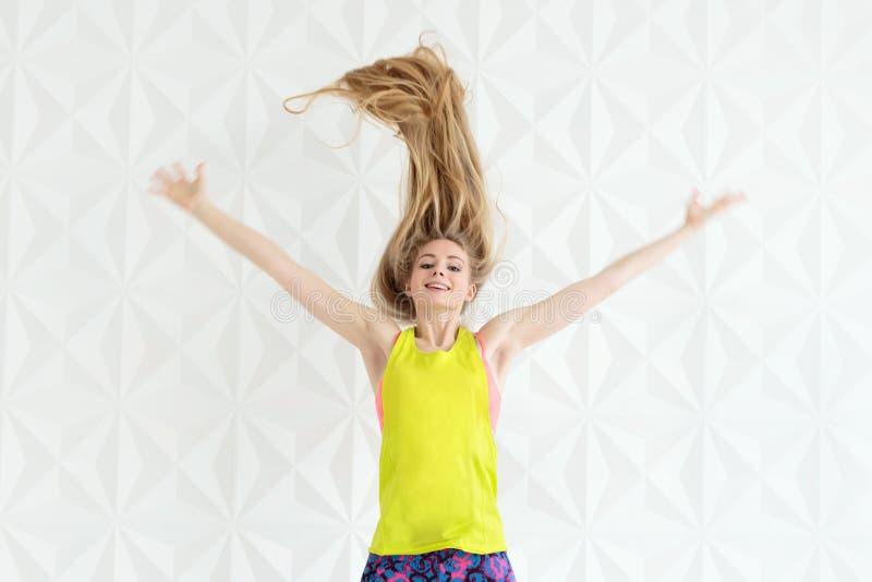 Close up da mulher apta de salto feliz com cabelo longo sobre a parede branca foto de stock