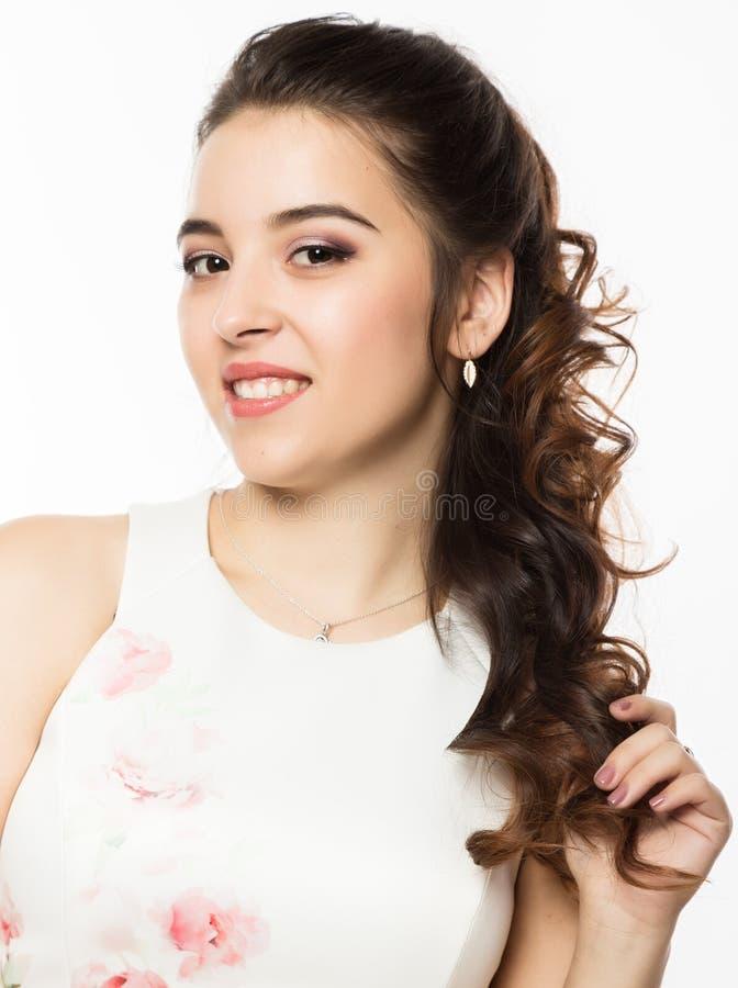 Close-up da mulher moreno nova no vestido branco no fundo branco Penteado profissional fotografia de stock