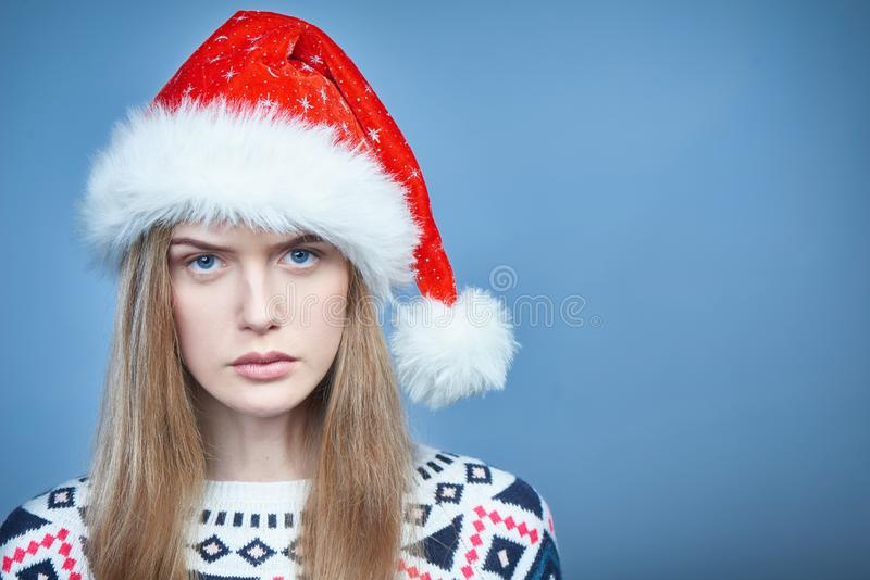 Close up da mulher olhando de sobrancelhas franzidas irritada que veste o chapéu de Santa fotografia de stock royalty free