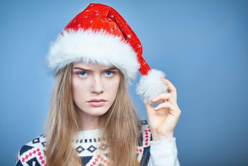 Close up da mulher olhando de sobrancelhas franzidas irritada que veste o chapéu de Santa imagem de stock