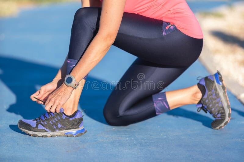 Close up da mulher que amarra laços de sapata Corredor fêmea da aptidão do esporte que prepara-se para movimentar-se fora fotos de stock