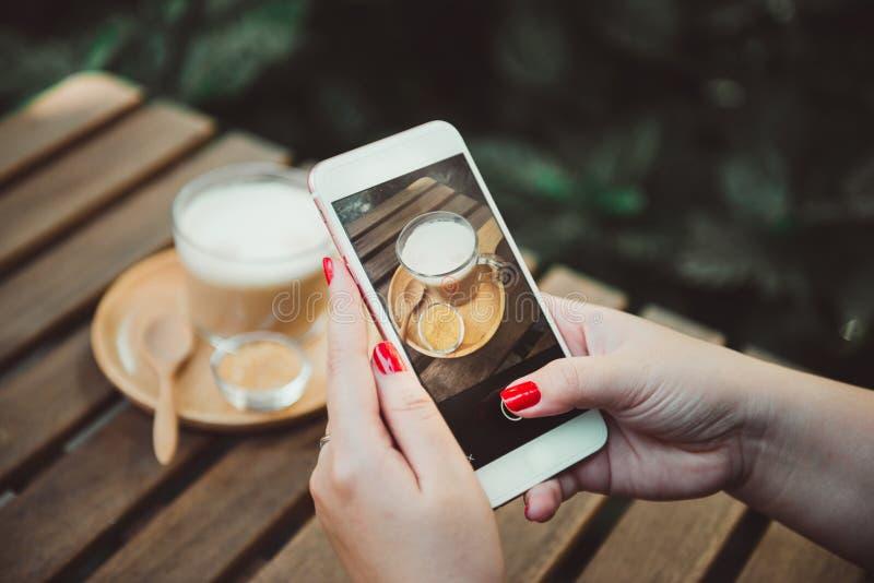 Close up da mulher que guarda e que mostra a tela de seu smartphone S fotografia de stock