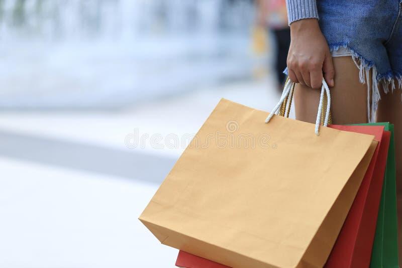 Close up da mulher que guarda sacos de compras com posição no depa imagens de stock