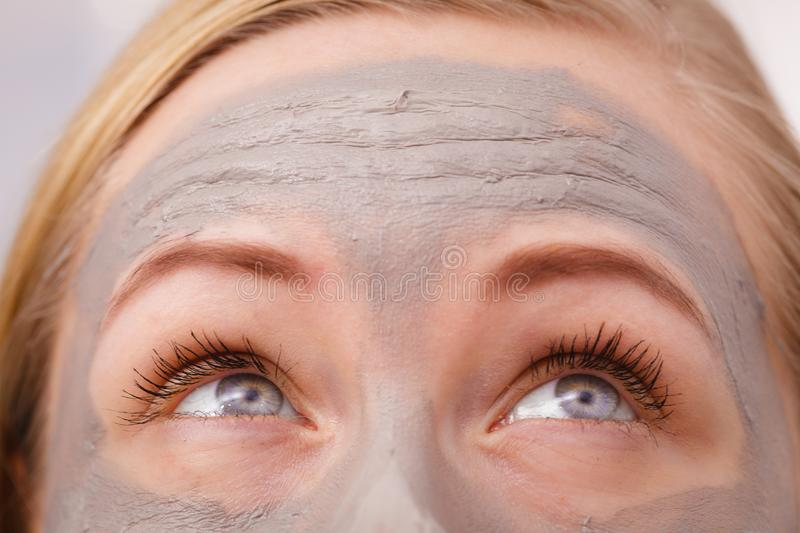 Close up da mulher que tem a máscara cinzenta da lama na cara fotografia de stock royalty free