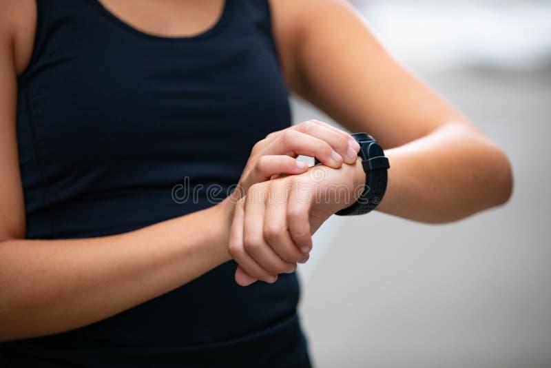 Close-up da mulher que usa o dispositivo esperto do relógio da aptidão antes de correr foto de stock
