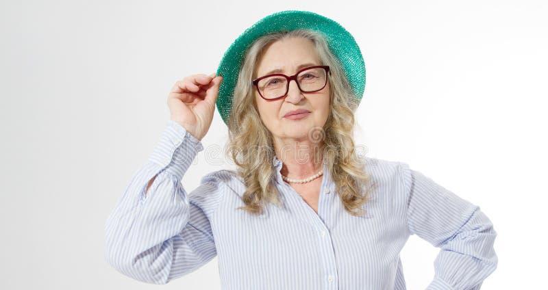 Close up da mulher superior à moda feliz em vidros do negócio e em chapéu do verão Positivo vivificante das pessoas adultas Saudá imagens de stock
