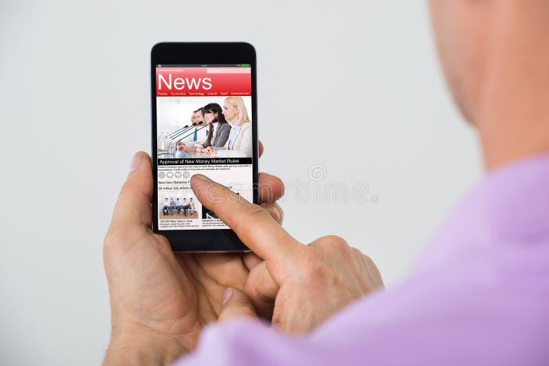 Close-up da notícia da leitura do homem em Smartphone fotografia de stock