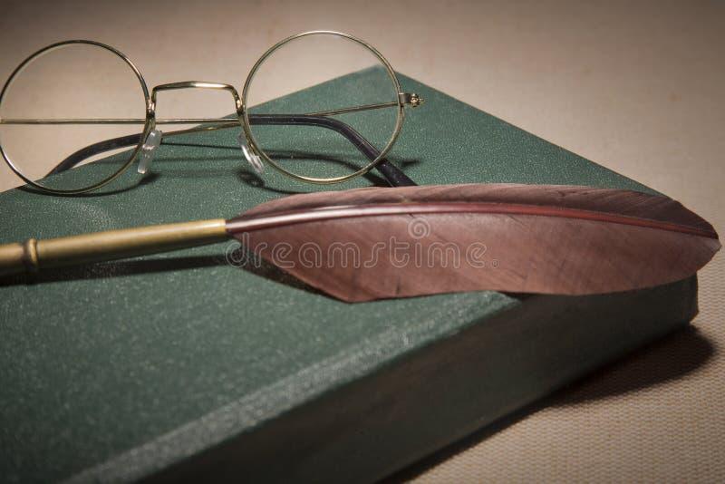 Close up da pena da pena da fonte com vidros do vintage no Livro Verde velho Foco seletivo imagens de stock