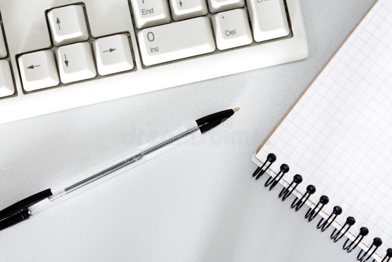 Close up da pena, do teclado e do caderno fotografia de stock