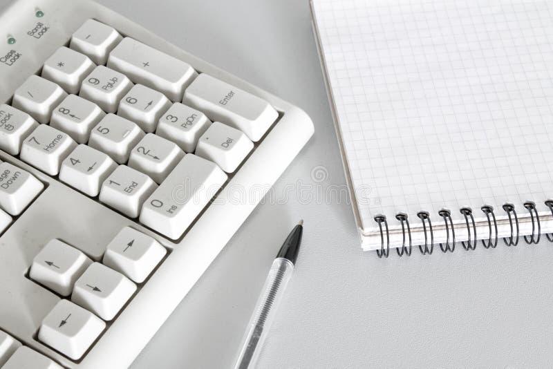 Close up da pena, do teclado e do caderno foto de stock royalty free