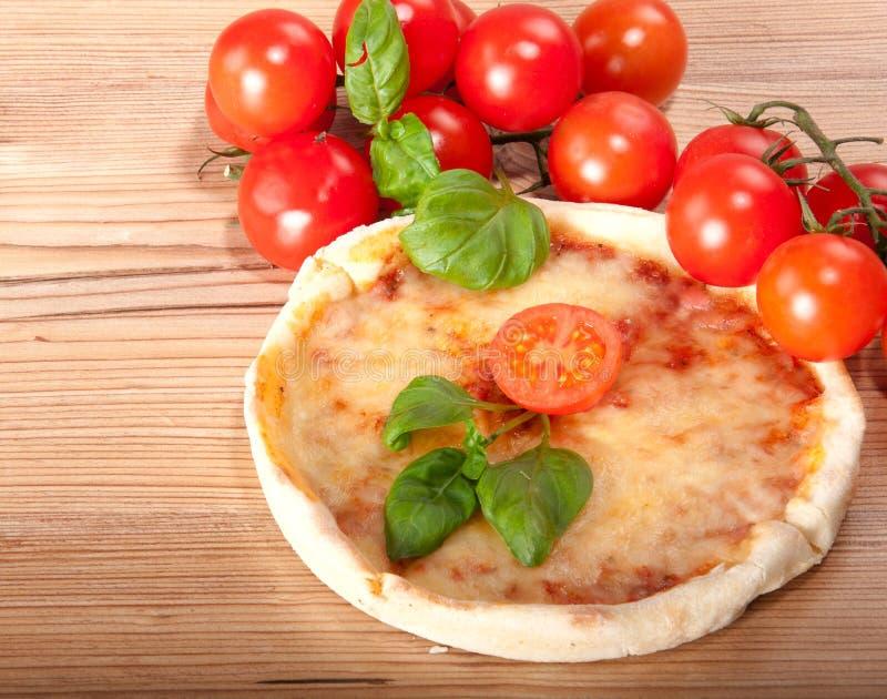 Close up da pizza com tomates, queijo e manjericão no fundo de madeira fotos de stock royalty free