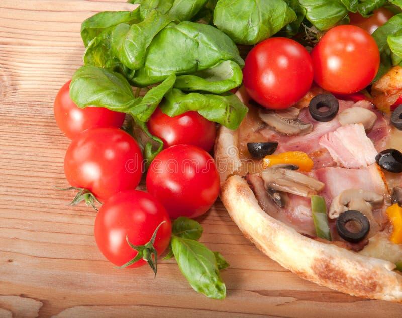 Close up da pizza com tomates, queijo e manjericão no fundo de madeira foto de stock