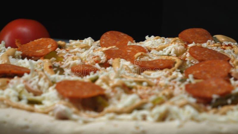 Close-up da pizza de Pepperoni que prepara e que adiciona o salame na massa coberta com o queijo, os pepinos conservados e o molh fotos de stock