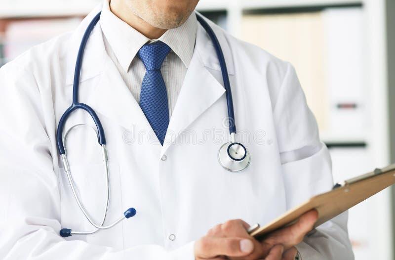 Close-up da prancheta com papel vazio na mão do médico O doutor masculino escuta o paciente que guarda uma prancheta fotografia de stock