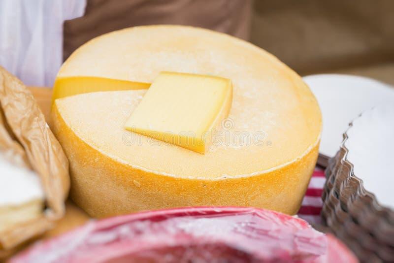 Close-up da roda do queijo e da parte cortada no contador do mercado Produto de leiteria fotos de stock