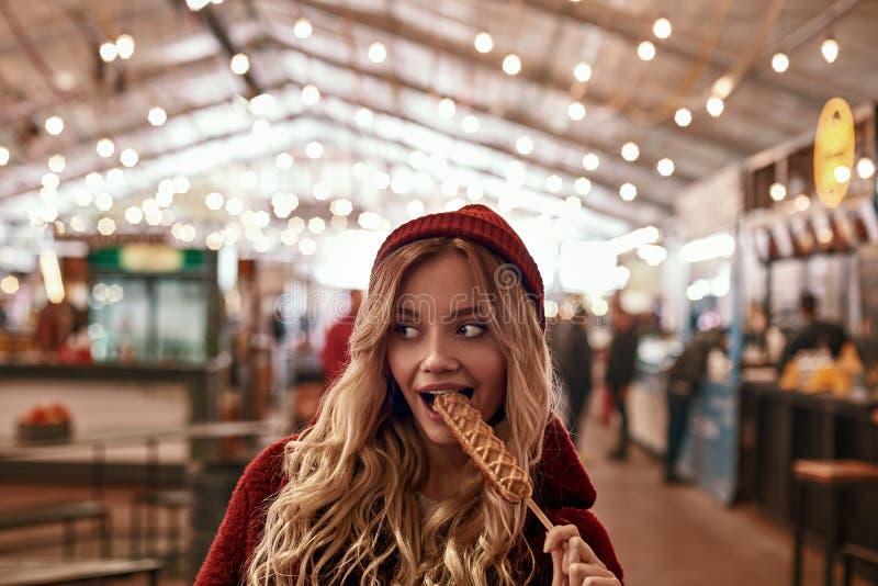 Close-up da salsicha eatting do vegetariano da mulher loura nova na massa imagem de stock