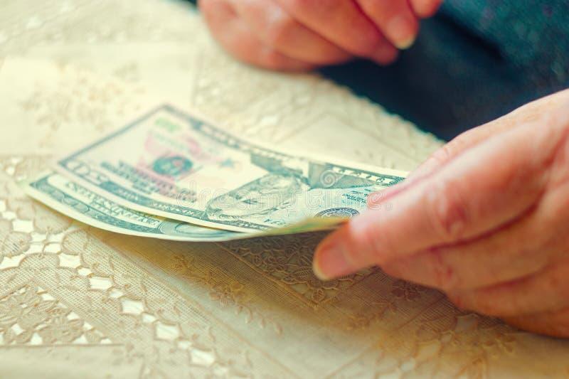 Close up da senhora superior com notas de dólar nas mãos, imagem tonificada instagram-como a cor, foco seletivo, DOF muito raso fotografia de stock royalty free
