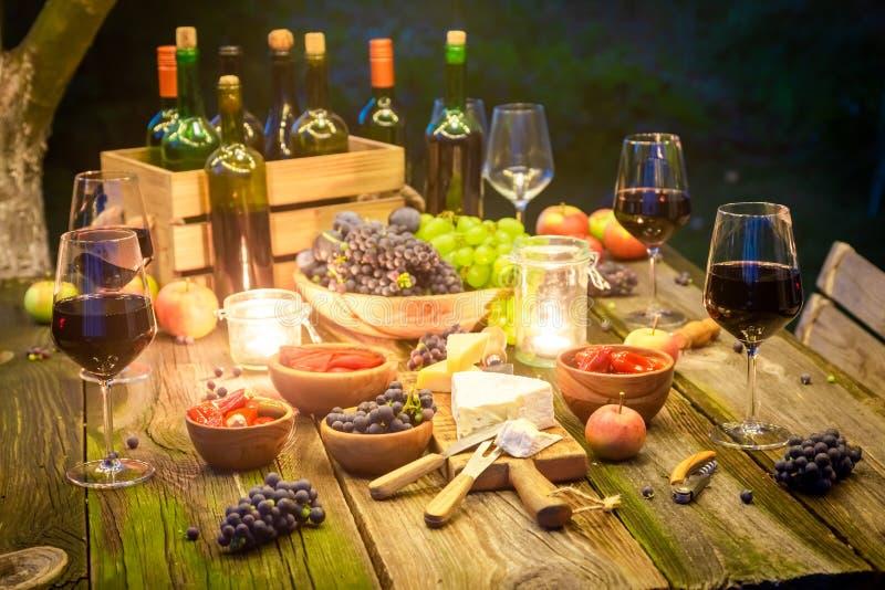 Close up da tabela com petiscos e vinho no jardim iluminado imagens de stock royalty free