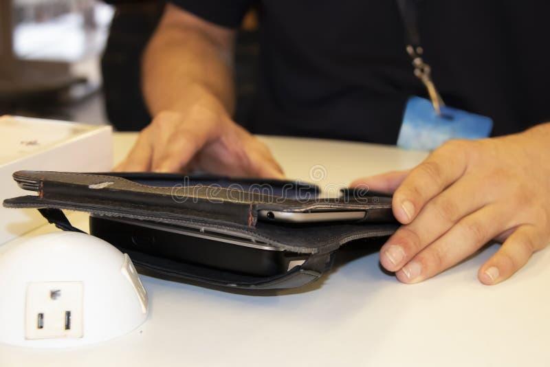 Close up da tabuleta no caso de couro com suporte na tabela com as mãos do trabalhador que ajudam um cliente - borrado imagem de stock
