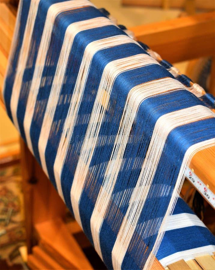 Close up da urdidura listrada azul e branca tecer Handweaving textiles fibra foto de stock