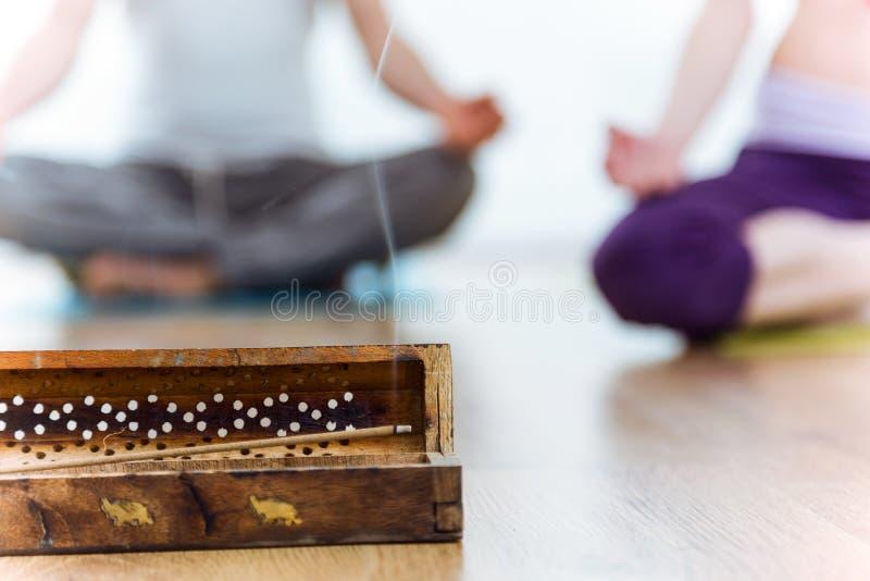 Close-up da vara do incenso, atrás dos pares que fazem a ioga fotos de stock royalty free