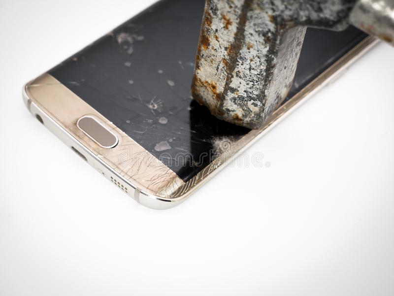 Close-up of damaged smartphone display with hammer royalty free stock photography