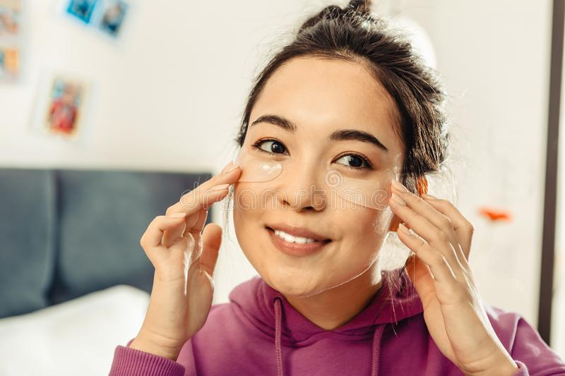 Close up of dark-eyed Asian woman taking care of her skin royalty free stock photos