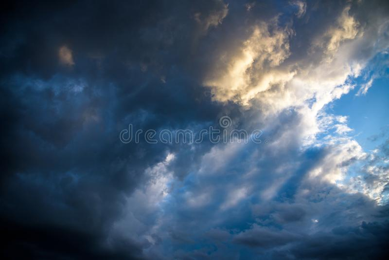 CLOSE UP: Dark grey stormy clouds gather above Lake Maggiore on a calm summer evening. Dramatic shot of clouds covering up the royalty free stock photo