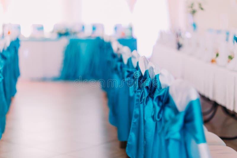 Close-up das cadeiras bonitas decoradas pela tela azul no restaurante Decorações do salão do casamento com fundo borrado foto de stock