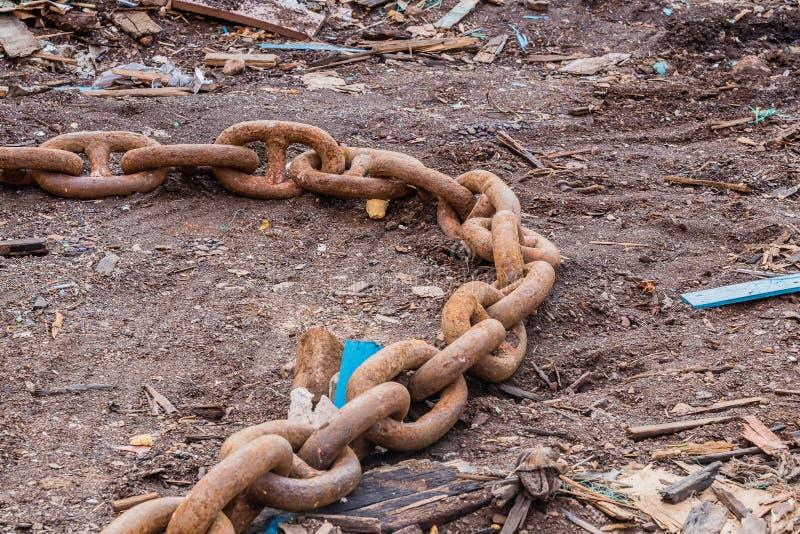 Close up das grandes correntes oxidadas que colocam na terra fotografia de stock