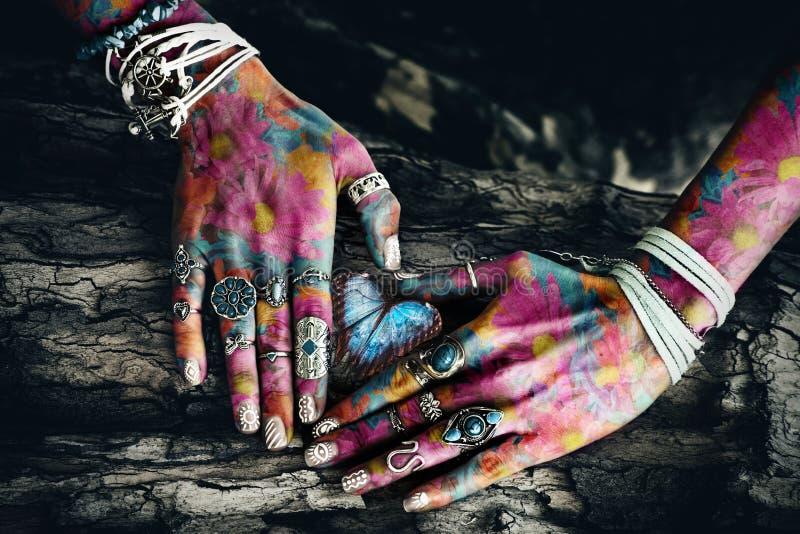 Close up das mãos coloridas da mulher na superfície da árvore na forma do coração fotos de stock