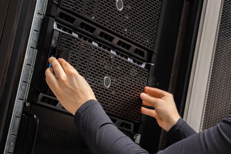 Close-up das mãos da cremalheira de Installing Servers In do consultante da TI em Datacenter fotos de stock royalty free