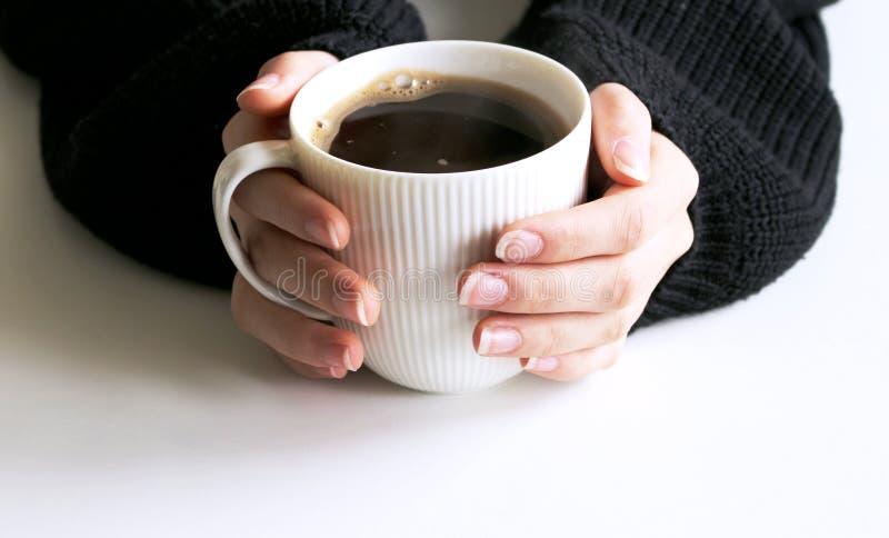 Close up das mãos da mulher na xícara de café feita malha preta da terra arrendada da camiseta Cena vazia do modelo da caneca Pro fotografia de stock royalty free
