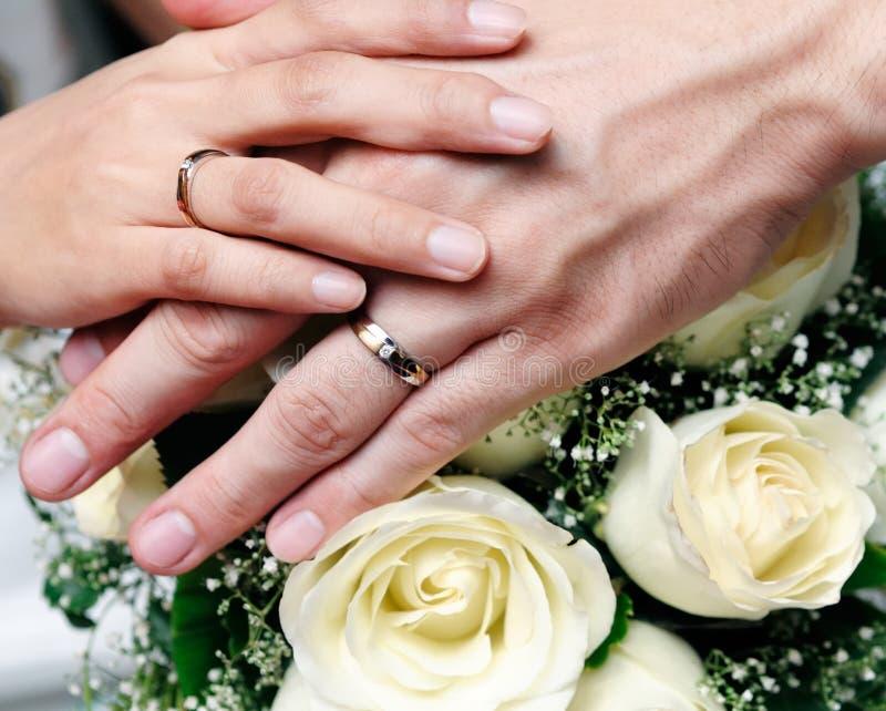 Close up das mãos da terra arrendada dos pares do newlywed imagem de stock