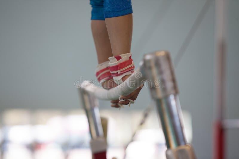 Close-up das mãos das correias das barras paralelas da menina da ginasta imagens de stock royalty free