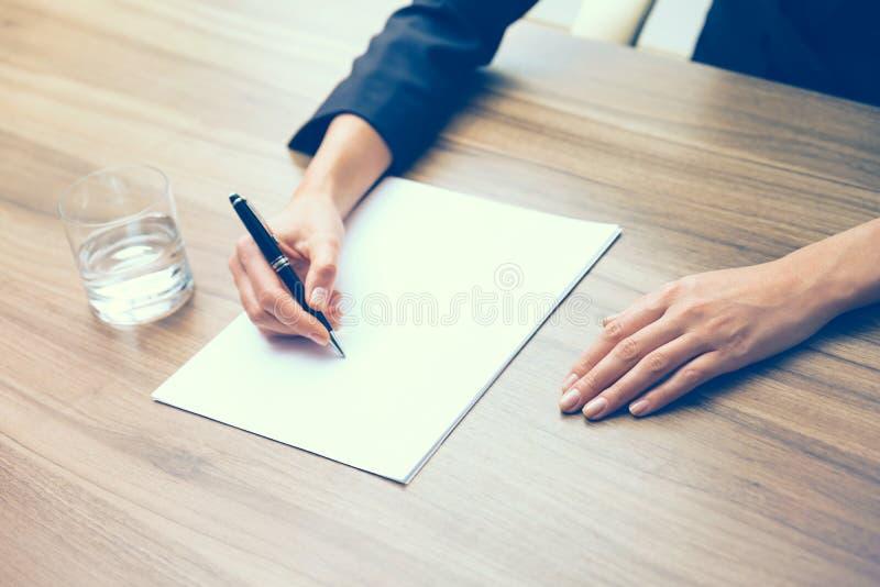 Close up das mãos de mulher de negócio ao redigir para baixo alguma informação essencial Um vidro da água, do papel e de uma pena fotografia de stock royalty free