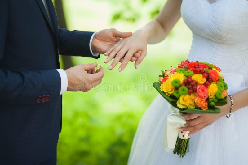 Close up das mãos de pares irreconhecíveis nupciais com alianças de casamento a noiva guarda o ramalhete do casamento das flores fotos de stock royalty free