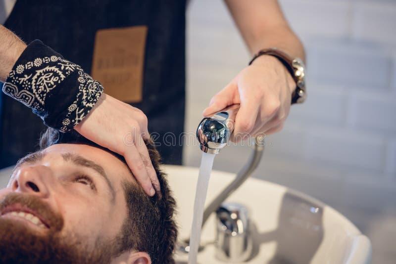 Close-up das mãos de um cabeleireiro especializado que dá uma lavagem do cabelo foto de stock royalty free