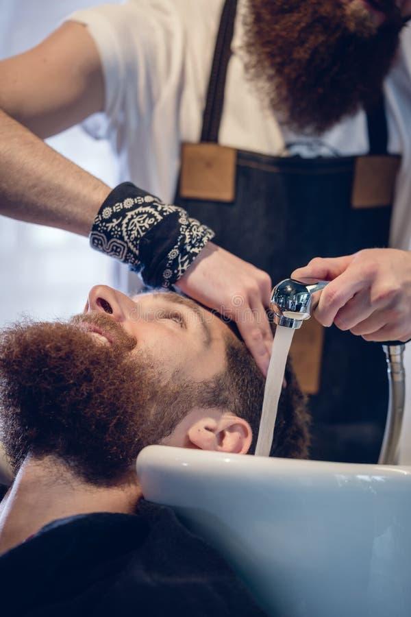 Close-up das mãos de um cabeleireiro especializado que dá uma lavagem do cabelo ao cliente fotos de stock royalty free