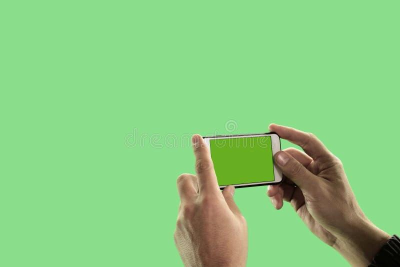 Close-up das mãos de um homem com um dispositivo em um fundo verde O indivíduo toma imagens ou dispara no vídeo em um telefone ce foto de stock