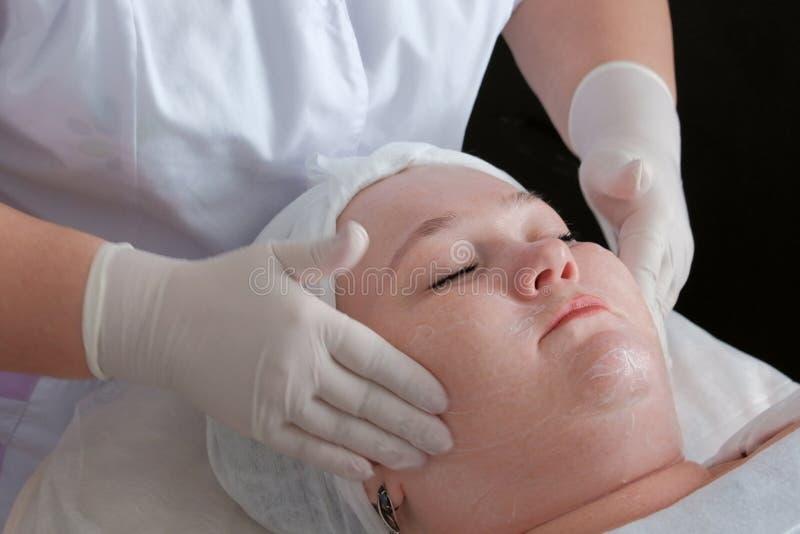Close-up das mãos de um sabão do esteticista a cara de uma mulher completa Procedimento da beleza de Cosmetological Pele que limp imagens de stock royalty free