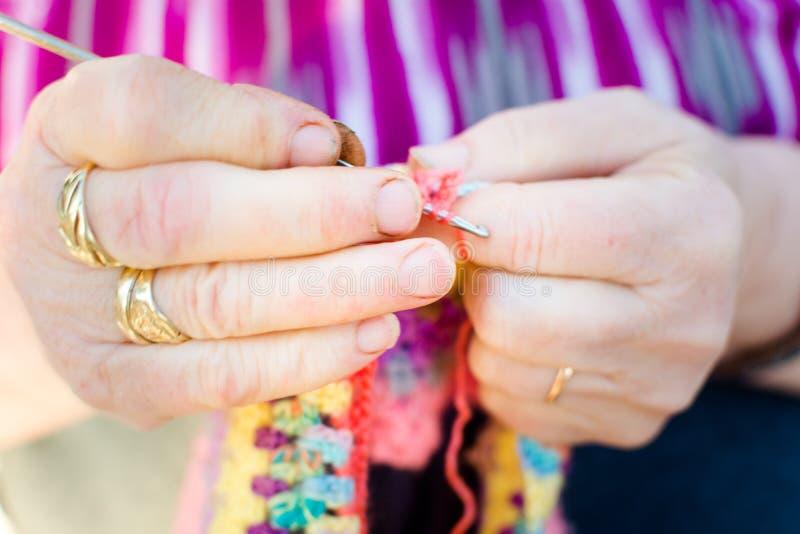Close-up das mãos de uma mulher adulta que faz malha em agulhas de confecção de malhas, usando lãs coloridas imagem de stock royalty free