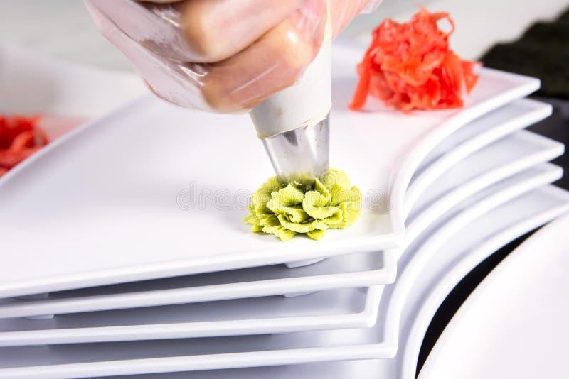 Close up das mãos do cozinheiro chefe que rolam acima do ajuste do sushi na placa na cozinha fotografia de stock royalty free