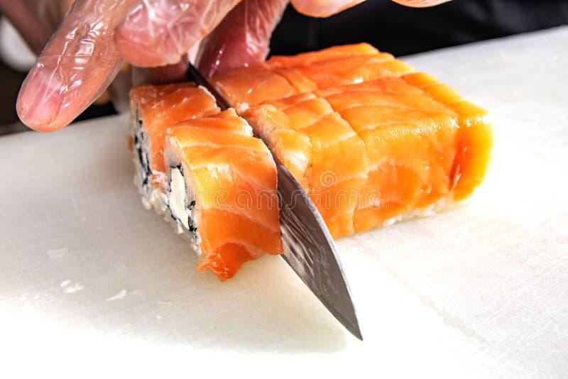 Close up das mãos do cozinheiro chefe que rolam acima dos cortes do sushi em parcelas na cozinha imagens de stock royalty free