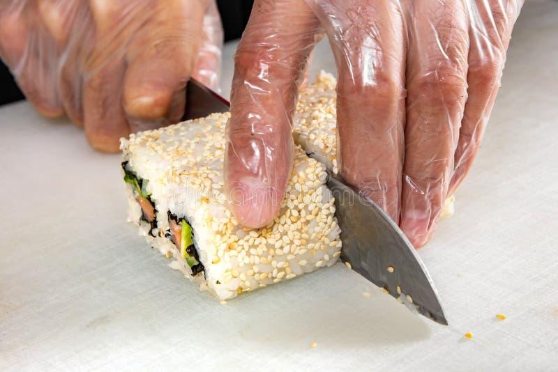 Close up das mãos do cozinheiro chefe que rolam acima dos cortes do sushi em parcelas na cozinha foto de stock royalty free