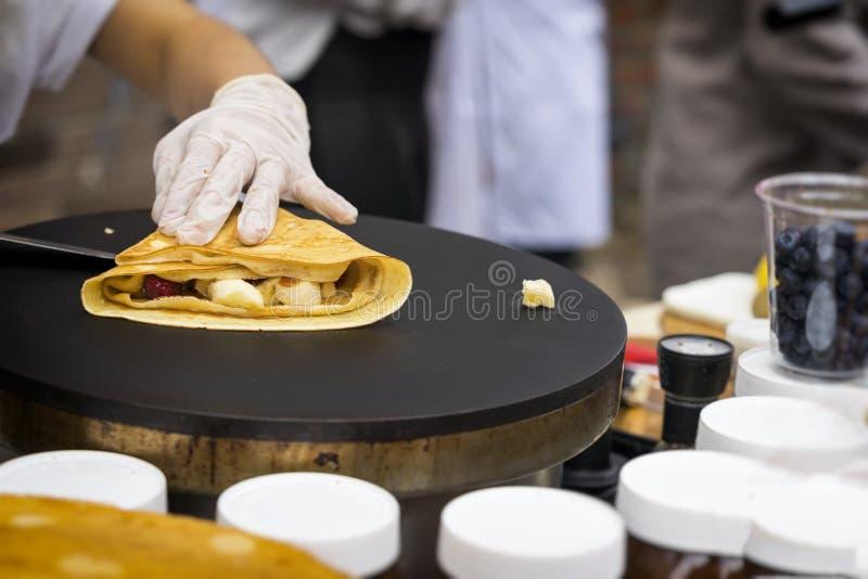 Close-up das mãos do cozinheiro na preparação das luvas rolada acima do crepe fino com fruto saboroso fresco na frigideira, molho imagens de stock